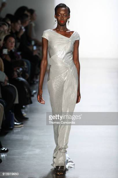 A model walks the runway wearing Tadashi Shoji Fall 2018 with makup by Pep Gay and hair by Kevin Ryan at Gallery I at Spring Studios on February 8...