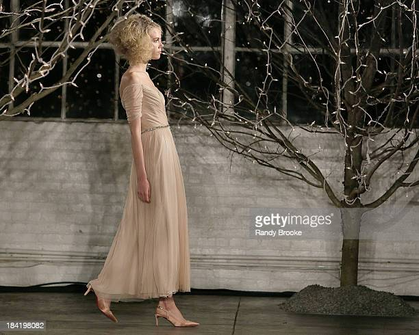 A model walks the runway wearing the first look during the Jenny Packham Fall 2014 Bridal collection show 25th anniversary reception on October 11...