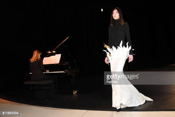 A model walks the runway when pianist ClaireMarie Le Guay performs during the Stephane Rolland Haute Couture Fall/Winter 20172018 show as part of...