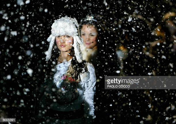 A model walks under artificial snow during Blumarine's underwear collection at ng Milan's Autumn/Winter fashion week 22 February 2004 AFP PHOTO/Paolo...