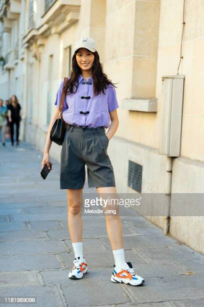 Model Wang Han wears a Billionaire boys Club cap, purple top, gray shorts, white socks, and Nike sneakers after the Zuhair Murad show during Couture...
