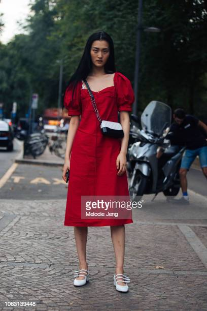 Model Wangy wears a red dress black and white purse and white flats during Milan Fashion Week Spring/Summer 2019 on September 22 2018 in Milan Italy