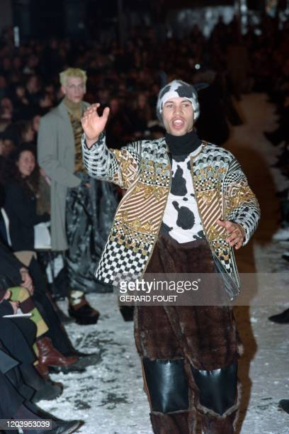 A Model waves to the crowd as he presents JeanPaul Gaultier's creations furry pants over large Siberianlike boots an embroidered checked ans striped...