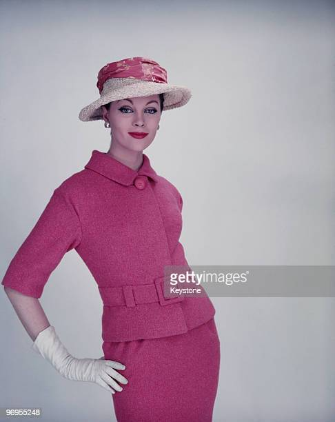 A model wearing a belted pink twopiece suit with a straw hat and white gloves circa 1955