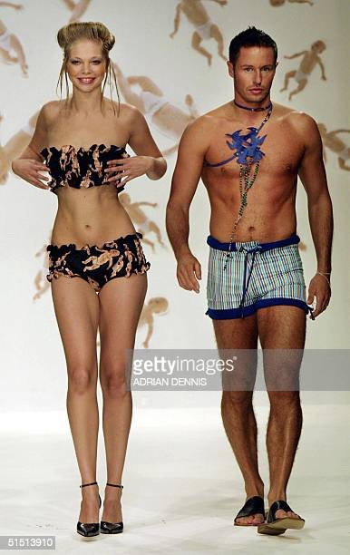 A model wearing a bikini alongside Big Brother television star Josh Rafter walk down the catwalk during Polish designer Arkadius show at London...
