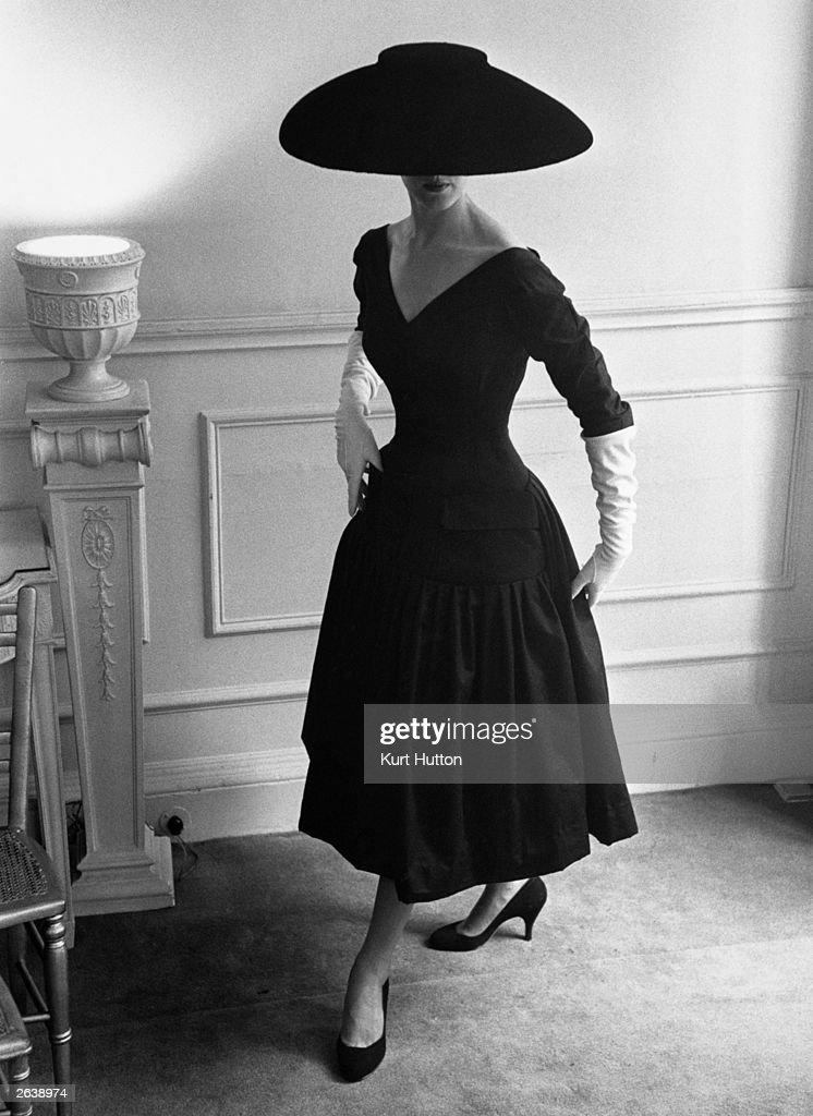 A model wearing a black cocktail dress and a black velvet wide-brimmed hat, designed by Ronald Paterson. Original Publication: Picture Post - 7974 - Designers Turn Critics - pub. 1955