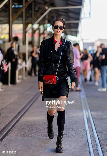 A model wearing a black dress college jacket and red bag outside By Johnny at MercedesBenz Fashion Week Resort 17 Collections at Carriageworks on May...