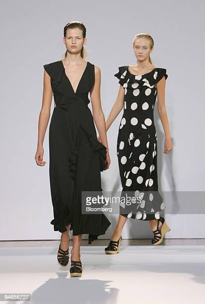 A model wearing a black fluid asymetric ruffle dress left and another wearing a super dot print ruffle dress walk down the catwalk during the showing...