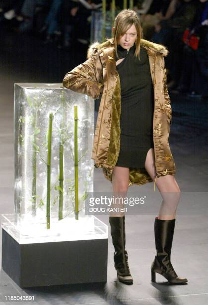 A model wearing a black georgette cheong sam and gold bamboo brocade coat stands next to a block of ice with bamboo at the Vivienne Tam Fall 2003...