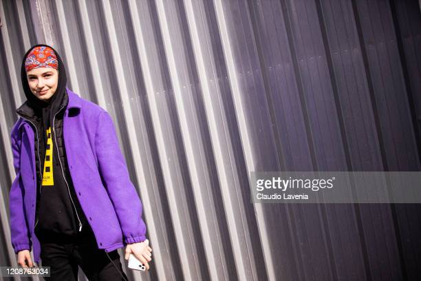 A model wearing a black Moncler sweatshirt purple jacket red printed hair scarf and black pants is seen outside Emporio Armani show during Milan...