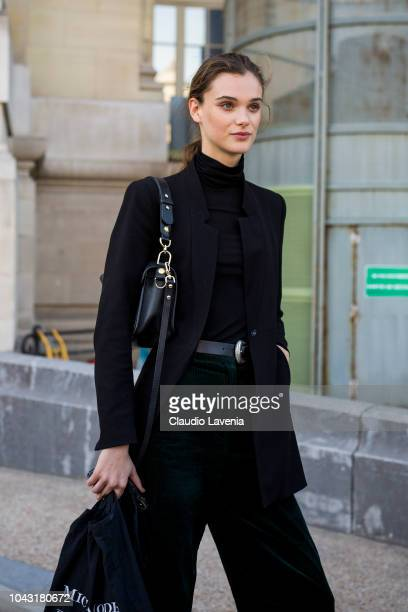 A model wearing a black turtleneck sweater black blazer green pants and black bag is seen after the Elie Saab show on September 29 2018 in Paris...