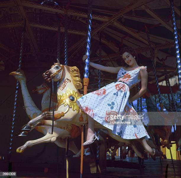 A model wearing a blue floral dress rides on the MerryGoRound at Battersea funfair