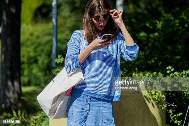A model wearing a blue white striped sweater and looking at her phone outside By Malene Birger during the second day of the Copenhagen Fashion Week...
