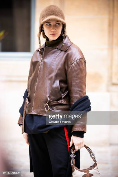 Model, wearing a brown leather jacket, black pants, beige fur hat and beige decorated bag, is seen outside Valentin Yudashkin, during Paris Fashion...