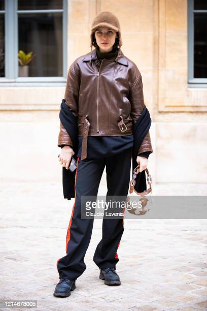 Model, wearing a brown leather jacket, black pants, black shoes, beige fur hat and beige decorated bag, is seen outside Valentin Yudashkin, during...