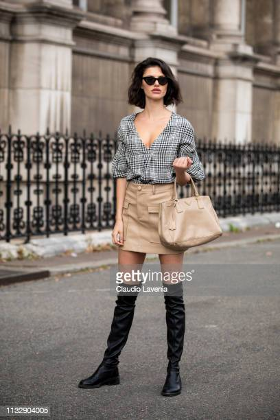 A model wearing a checked shirt beige mini skirt beige bag and black over the knees boots is seen outside Redemption on Day 4 Paris Fashion Week...