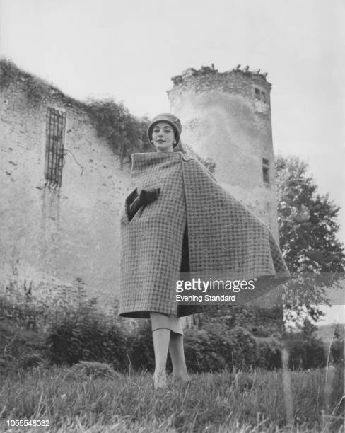 Model wearing a checked tweed cape by French fashion designer Hubert de Givenchy, February 1957. The cape features an armhole for carrying a handbag.