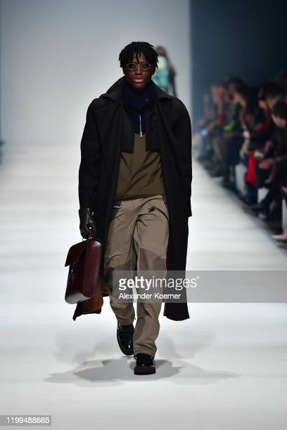 Model wearing a coat by Brachmann, vest by Arys, trousers by Klaettermusen, collar by Christina Kraemer, bag by Ackermann, glasses by Neubau Eyewear,...