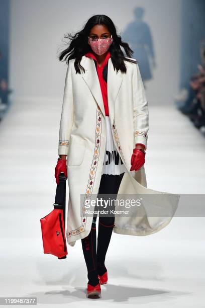 Model wearing a coat by Suri x Saheli Women Collaboration, vest by Klaettermusen, hoodie by Stoffbruch, skirt by Gaya, leggings by Ambiletics, bag by...