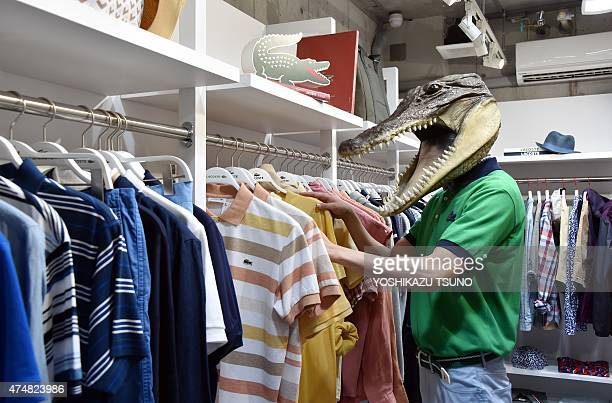 A model wearing a crocodile mask checks a polo shirt of the new collection from French casual fashion brand Lacoste in Tokyo on May 27 2015 AFP PHOTO...