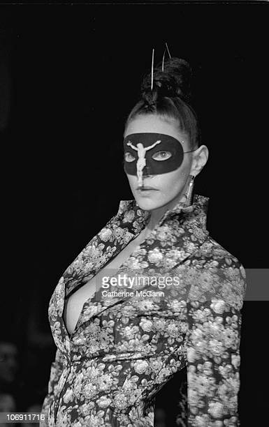 Model wearing a crucifix mask walks the runway at British fashion designer Alexander McQueen's first New York fashion show at a former synagogue on...
