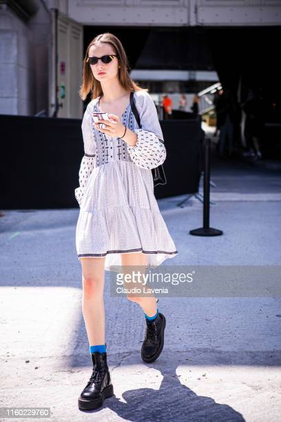 Model, wearing a decorated dress and black boots, is seen outside Chanel show during Paris Fashion Week - Haute Couture Fall/Winter 2019/2020 on July...