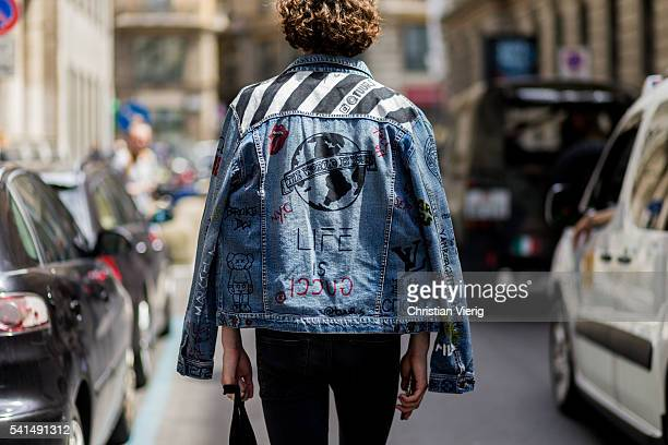 A model wearing a denim jacket with prints outside Ferragamo during the Milan Men's Fashion Week Spring/Summer 2017 on June 19 2016 in Milan Italy