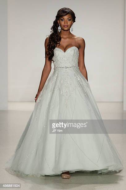 A model wearing a dress inspired by Disney character Tiana from The Princess and the Frog walks the runway wearing Disney Fairy Tale Weddings by...