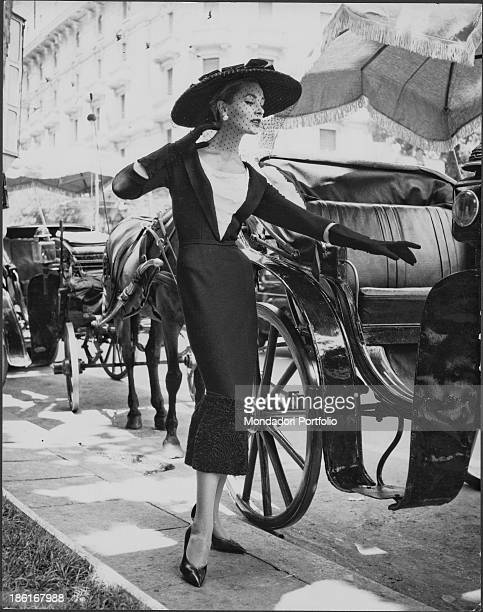 A model wearing a dress with three quarter length gloves and a hatveil from Fontana sisters' fashion collection Rome 1950s