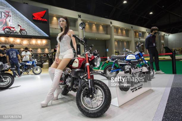 Model wearing a face shield as a precaution sit on a Honda Monkey 125 motorcycle at the Monkey Custom by Cub House stand inside the Honda stand...