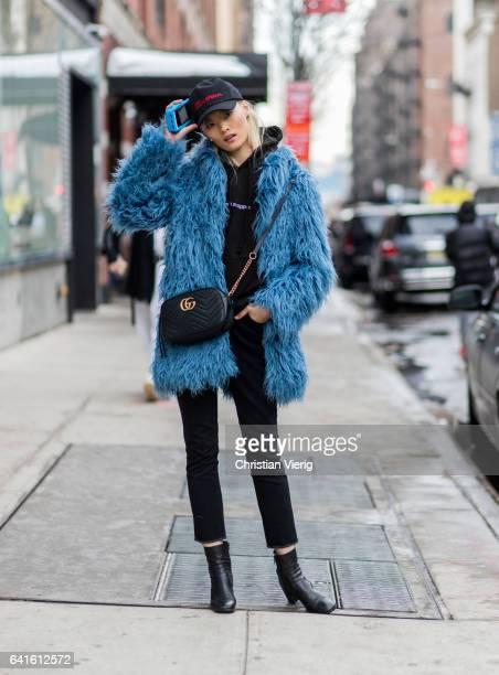 A model wearing a fake fur coat Gucci bag flex capt outside Tibi on February 11 2017 in New York City