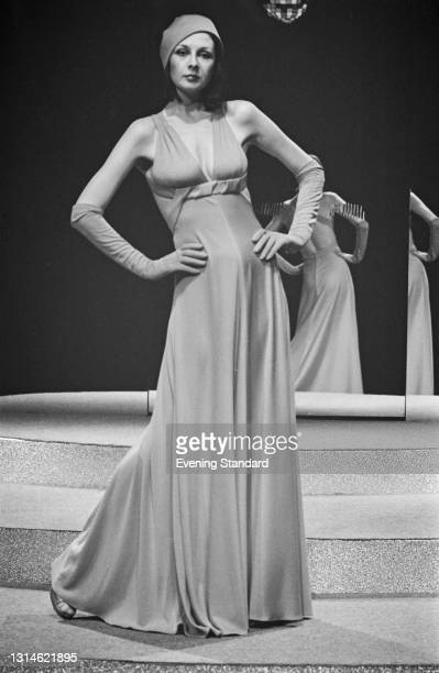 Model wearing a figure-hugging evening dress with evening gloves and a cap, UK, 8th April 1974.