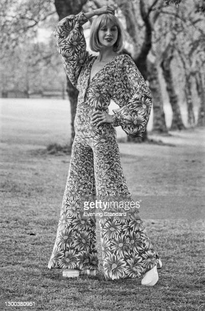 Model wearing a flared trouser suit in a floral fabric, UK, 1st May 1972.