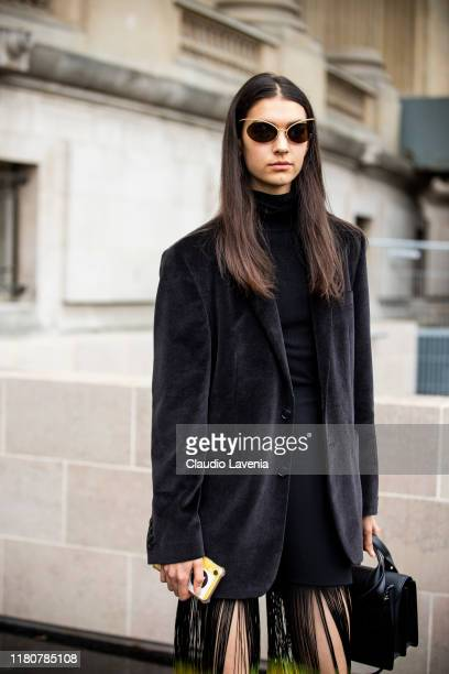 A model wearing a fringed black mini dress and black velvet blazer is seen outside the Chanel show during Paris Fashion Week Womenswear Spring Summer...