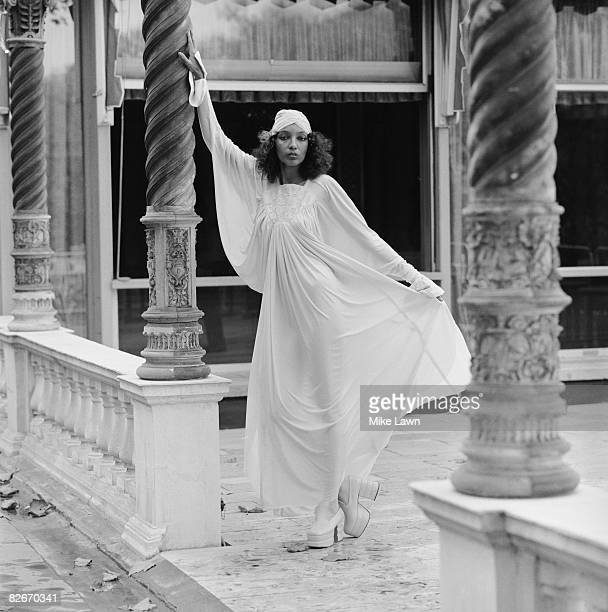 A model wearing a fulllength white dress with matching hat at a show by British designers Bill Gibb John Bates Jean Muir and Zandra Rhodes at Les...