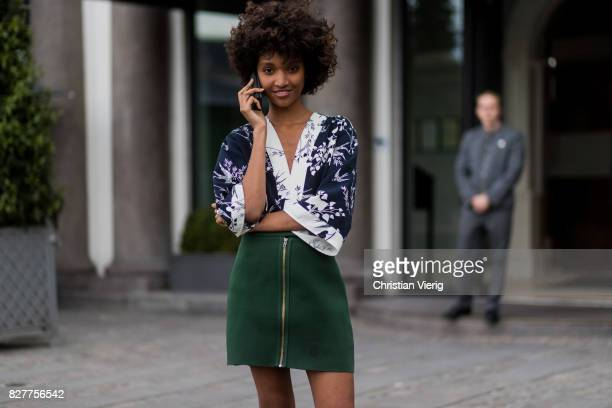 A model wearing a green skirt blouse with floral print outside Designers Nest on August 8 2017 in Copenhagen Denmark