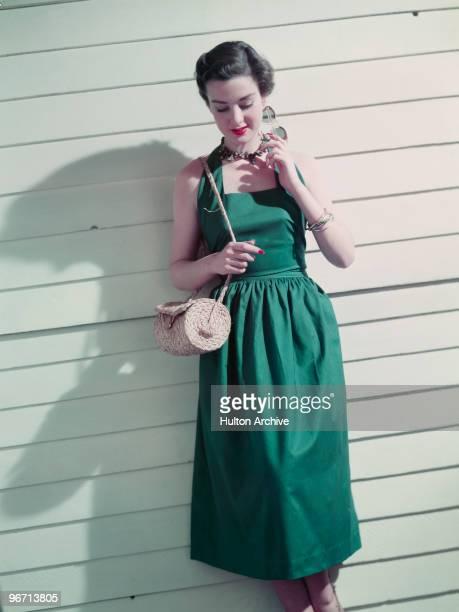 A model wearing a green summer dress with a plaited straw handbag June 1951