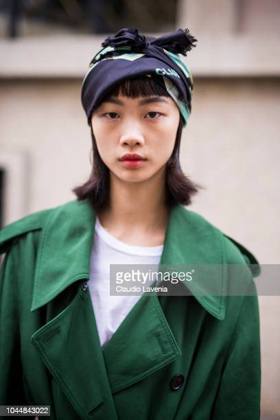 A model wearing a green trench coat and a printed headscarf is seen after the Miu Miu show on October 2 2018 in Paris France