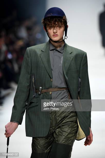 Model wearing a jacket by Aftermarch, shirt by Arys, trousers by Timberland and hat by Spatz Hutdesign walks the runway at the Neonyt show during...