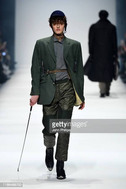 Model wearing a jacket by Aftermarch, shirt by Arys, trousers by Timberland, hat by Spatz Hutdesign and shoes by Vintage walks the runway at the...