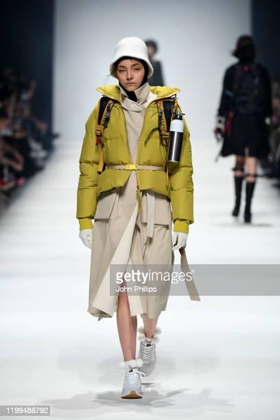 Model wearing a jacket by Langer Chen, coat by People Berlin, hood by Falke, hat by Sandermann, socks by Swedish Stockings, belt by People, backpack...