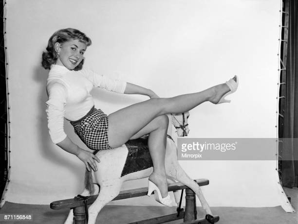 A model wearing a jumper and shorts posing on a rocking horse 1954