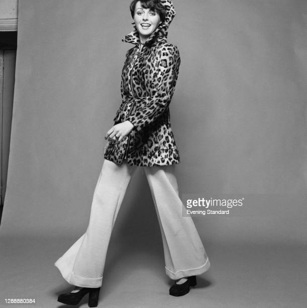 Model wearing a leopard print coat and flared trousers, UK, 9th December 1971.