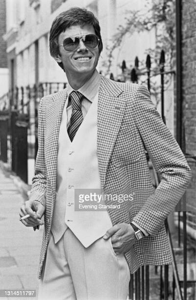 Model wearing a light-coloured waistcoat and trousers and a checked jacket, UK, 15th May 1974.