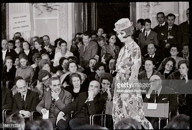 A model wearing a long flowered dress and a hat catwalking at Palazzo Pitti Florence 1960s