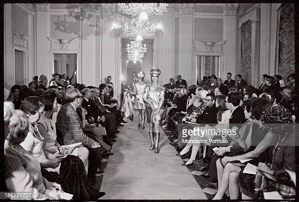 A model wearing a metallic dress and a strange headdress catwalking at Palazzo Pitti Florence 1960s