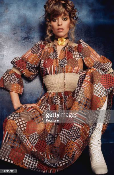 A model wearing a patchwork pattern dress with white laced boots circa 1975