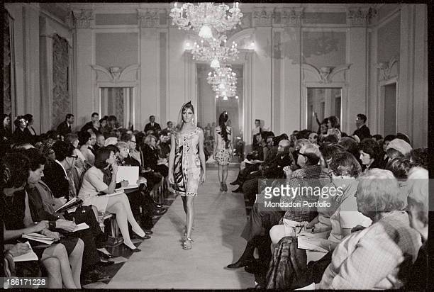 A model wearing a patterned dress and a pair of flipflop catwalking at Palazzo Pitti Florence 1960s
