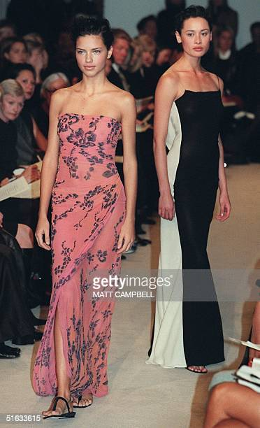 A model wearing a pink and silver fulllength chiffon dress walks past a model wearing a black and white fulllength dress during the Vera Wang fashion...