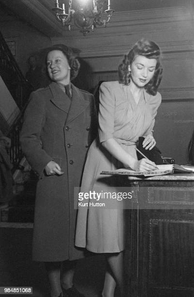 A model wearing a pistachio crepe dress with draped bodice at a fashion show held at the American Club in Grosvenor Square London February 1944 The...